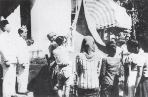 The flag-raising ceremony immediately after Sukarno read the Proklamasi at 10 a.m. on 17 August. The flag was sewn by Sukarno's wife Fatmawati the evening before. Sukarno and Hatta are standing to the left.