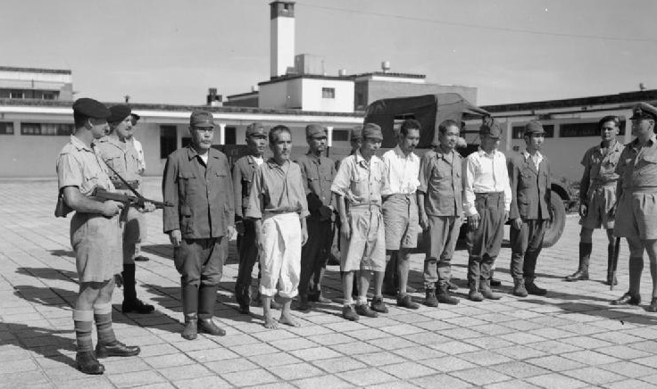 under guard while awaiting transfer to Stanley Prison, Hong Kong, 29 September 1945